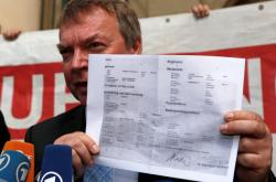 Kapitán Claus-Peter Reisch drží certifikát o registraci lodi Lifeline