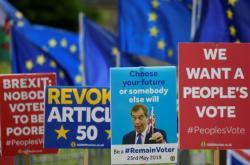 Evropské vlajky a transparenty proti brexitu u britského parlamentu