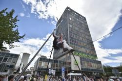 Demonstrantka visí na konstrukci před hlavní vjezdem do elektrárny Chvaletice