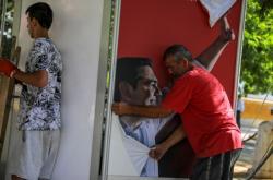 Volby v Řecku. Sundání plakátu s odcházejícím premiérem Alexisem Tsiprasem