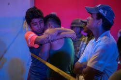 Mladí Mexičané se utěšují před vyhořelým barem