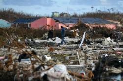 Muž prochází troskami ve městě Marsh Harbour
