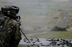 Střelba z lehkého kulometu FN Minimi. Na pravé straně fotky jsou vidět odlétávající nábojnice a článek pásu
