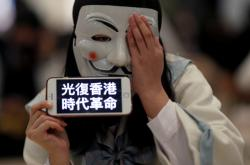 Pod maskami často skrývají své tváře i účastníci protivládních protestů v Hongkongu