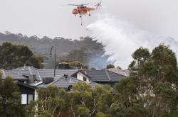 Helikoptéra shazuje vodu na předměstí Melbourne v Austrálii