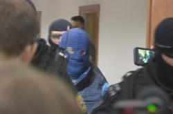 Zoltán Andruskó (v modré kukle) je přiváděn k soudu