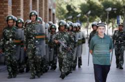 Policejní hlídka a jeden z Ujgurů v Urumči
