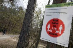Cedule vyzývající k dodržování odstupu v berlínském lese