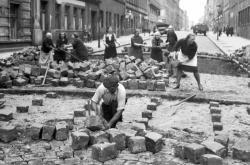 Ženy na Vinohradech pomáhají při práci dlaždičům v pražské Belgické ulici (snímek z 26. září 1945)