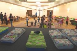 V suterénu kostela spí děti na pódiu