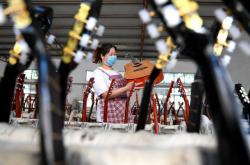 Pracovnice kontroluje kytaru v továrně na hudební nástroje v Číně