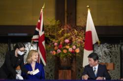 Britská ministryně obchodu Liz Trussová a japonský ministr zahraničí Tošimicu Motegi při podpisu smlouvy