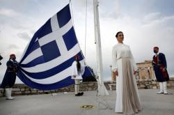 Členové prezidentské stráže vztyčují v rámci oslav řeckou vlajku na vrcholu Akropole