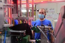 Pracovník osazuje šrouby do pouzder světlometů v závodě firmy Montix