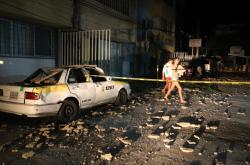 Pár míjí taxík, který byl poškozen padajícími úlomky po silném zemětřesení v mexickém Acapulcu