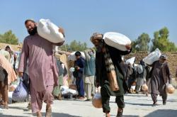 Lidé v Kandaháru si nosí humanitární pomoc
