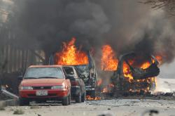 Hořící auta po útoku na organizaci Save the Children