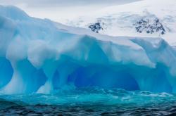 Tučňáci se škrábou na vrcholek ledovce na ostrově Danco, Antarktida