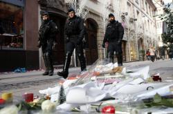 Policejní hlídka prochází kolem květin položených na místě úterního útoku