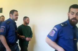 Dominik Kobulnický s policisty u soudu