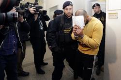 Jeden z vazebně stíhaných Nizozemců odchází v doprovodu eskorty od soudu.