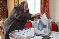 Obyvatelka Lvovské oblasti hází lístek do přenosné urny