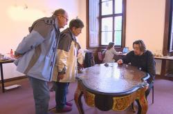Návštěvníci zámku sledují restaurátora při práci