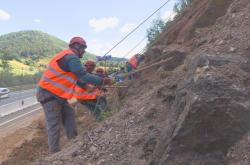 Horolezci zajišťují skálu u frekventované silnice
