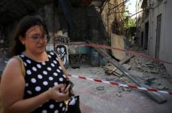 Žena prochází v Aténách kolem budov, které poničilo zemětřesení