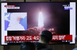 Lidé na nádraží v jihokorejském Soulu sledují zprávy o vypálení raket v Severní Koreji
