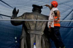 Čištění Koněvovy sochy před tím, než dostala nátěr proti barvám