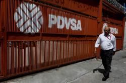 Muž prochází kolem brány s logem venezuelské státní firmy PDVSA