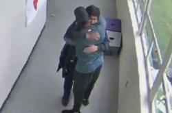 Trenér (zády ke kameře) objímá žáka poté, co ho odzbrojil