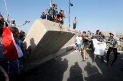 Demonstranti strhávají zeď v Bagdádu