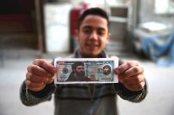 Mladý Syřan drží v roce 2015 bankovku s portrétem Bagdádího