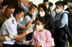 Zdravotnický personál kontroluje cestující na letišti v Bangkoku