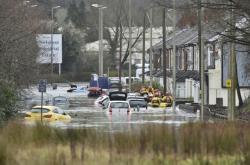 Lidé před zatopeným domem na Oxford Street v Nantgarw ve Walesu.