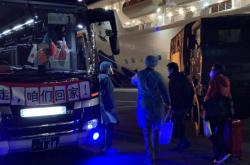 Autobus čekající na cestující, kteří opustili loď Diamond Princess