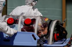 Jihokorejští zdravotníci převážejí jednoho z nakažených koronavirem