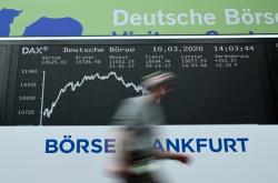 Muž prochází kolem tabule s indexem DAX frankfurtské burzy