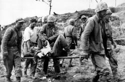 Američtí vojáci nesou raněného na nosítkách