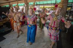 Thajské tanečnice ve svatyni Erawan v Bangkoku nosí obličejový štít, aby pomohli omezit šíření koronaviru.