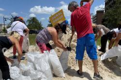 Lidé ve floridském městě Doral plní pytle s pískem