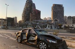 Poškozené auto stojí po výbuchu na ulici v Bejrútu