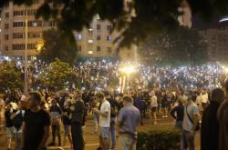 Lidé, demonstrující v centru Minsku, drží nad hlavami svítící displeje svých telefonů