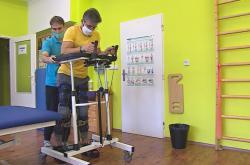 Paraplegik s exoskeletem v chodítku