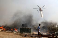 Požární helikoptéra hasí vzniklý oheň jihovýchodně od Atén
