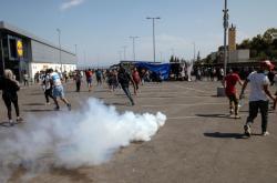 Migranti utíkají před slzným plynem