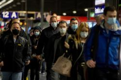 Lidé s rouškami na vlakovém nádraží ve Frankfurtu