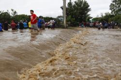 Lidé poblíž honduraské Limy čekají, až budou zachráněni
